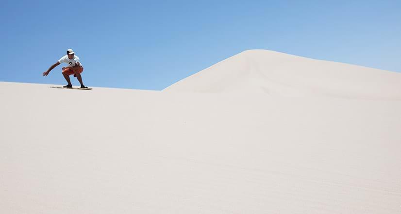 Sandboarding en las dunas cerca a la laguna Huacachina.